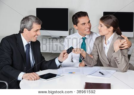 Consultant in his office offering business card to couple