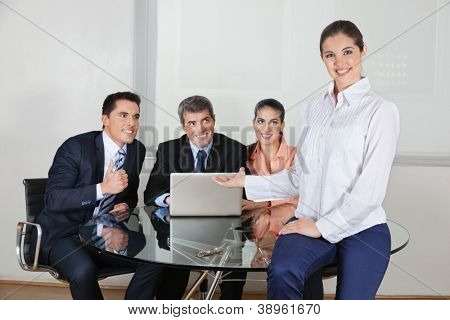Smiling business woman presenting her office team with laptop computer