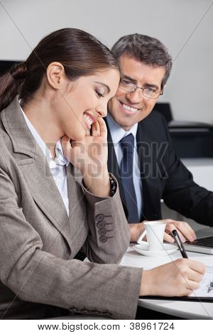 Happy attractive business woman taking notes in the office