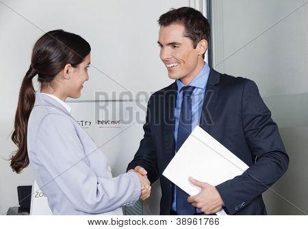 Homem de negócios e mulher dando aperto de mão no escritório