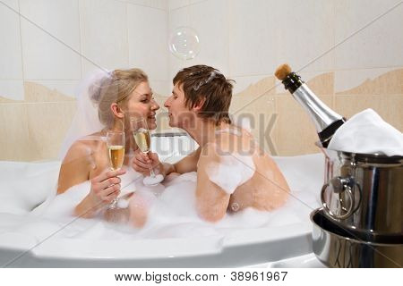 A young beautiful couple is enjoying a bath with champagne in a glass and kissing. Bubbles are floating in the air