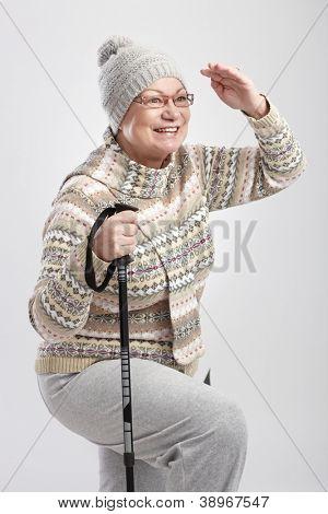Ältere Dame auf Abstand halten Wander Stöcke, lächelnd.