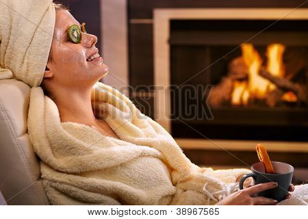 Smiling woman relaxing at home with kiwifruit facial mask and tea mug, sitting in bathrobe in front of fireplace.