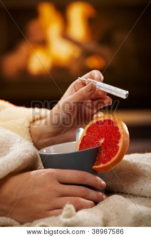 Checking temperature, illness, winter cold, female hands holding tea mug with blood orange and thermometer in front of fireplace.