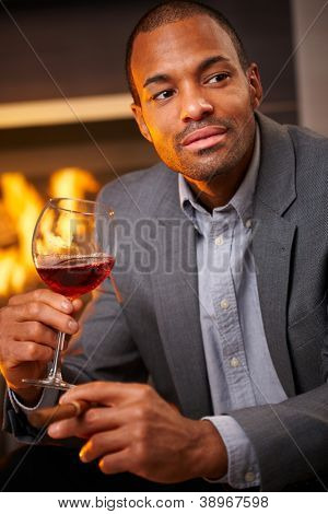 Handsome black man sitting by fireplace smoking cigar, drinking wine.