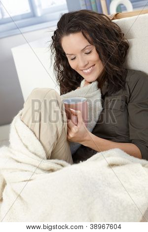 Happy woman cuddling with blanket, sitting with tea mug, smiling.
