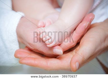 Parental hands holding legs of the baby