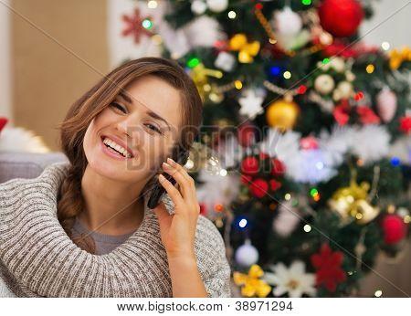 Mulher feliz perto de árvore de Natal, fazer chamada de telefone