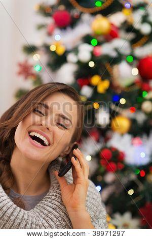Mulher sorridente perto de árvore de Natal, fazer chamada de telefone