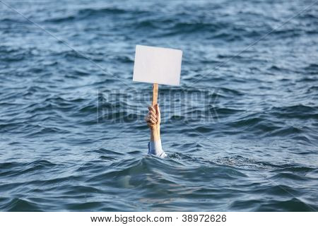 Hand with blank banner among a sea