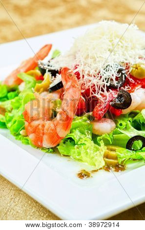 Salad with shrimps, caviar, calamaries, lettuce, olive, tomato and mozzarella