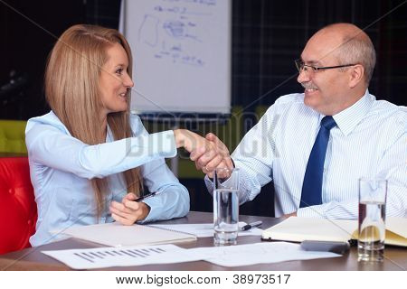 Young attractive businesswoman shake hands with senior businessman, background in the office