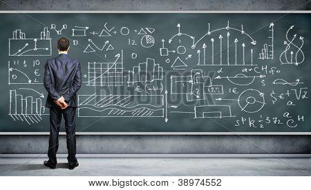 Geschäftsperson, die gegen die Tafel mit einer Menge von Daten, die geschrieben stehen