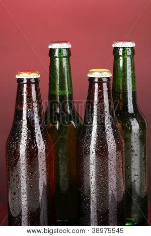 Coloured glass beer bottles on red background