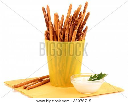 Tasty crispy sticks in yellow plastic cup isolated on white