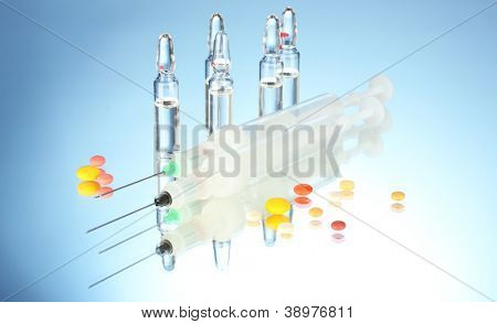 syringes monovet, ampoules and pills on blue background