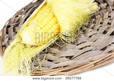 Fresh corn cob on wicker mat isolated on white