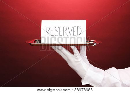 Hand in glove holding silver tray with card saying reserved on red background
