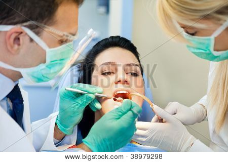 female patient with open mouth receives an injection at the dentist