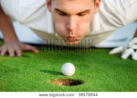 golfer lying on grass and blowing in the ball,  just need to give it a little help.