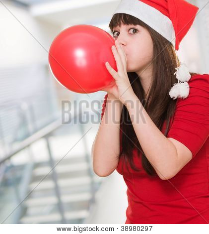 woman wearing a christmas hat and blowing a balloon, indoor