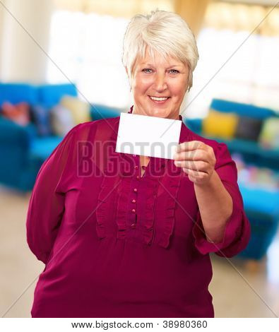Portrait Of A Senior Woman Holding A Blank Card, Indoor