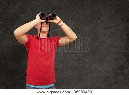 portrait of young man with binoculars against a grunge wall