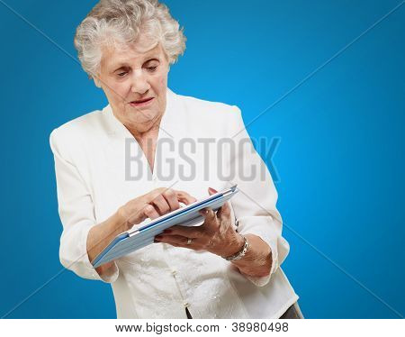 Senior woman using ipad isolated on blue background