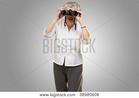 Portrait of a senior woman looking through binoculars on grey background