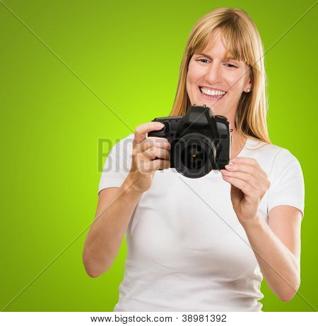 Happy Young Woman Looking At Camera against a green background