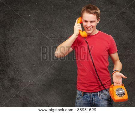 retrato de jovem homem falando no telefone vintage contra uma parede de grunge