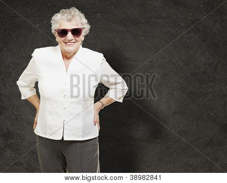 portrait of senior woman standing wearing sunglasses against a grunge wall