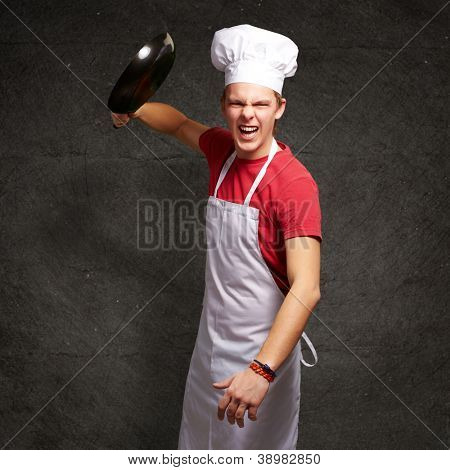 portrait of angry young cook man hitting with pan against a grunge wall