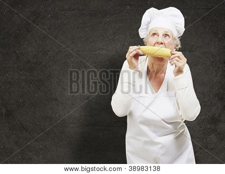 senior woman cook eating a corncob against a grunge background