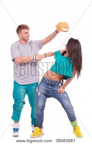 hip hop couple, man trying to put his hat on the woman's head while shaking hands...goofing around on white background