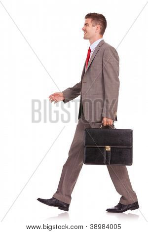 side view of a business man with briefcase walking and smiling, isolated on white