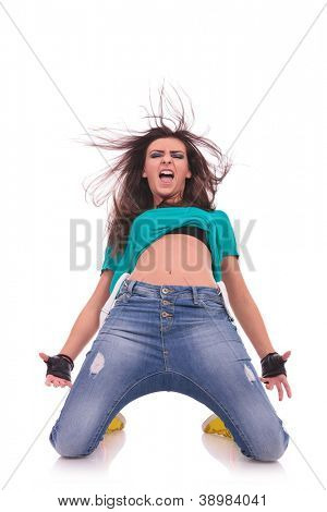 young woman dancer posing on her knees and shouting, isolated on white background