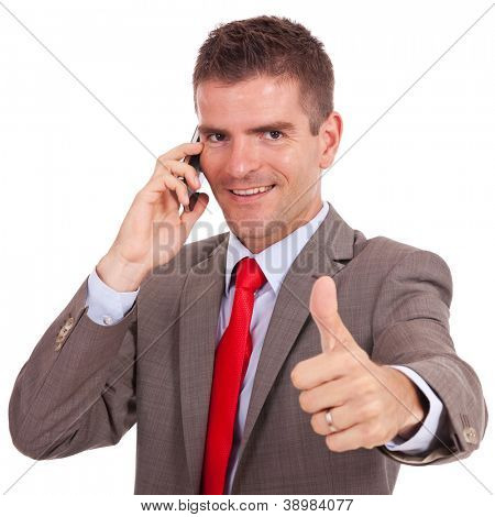 smiling young business man talking on the phone and making ok gesture. Isolated on white background