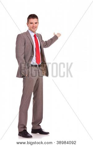 Happy business man presenting something in his back, with a hand in his pocket. isolated on white background