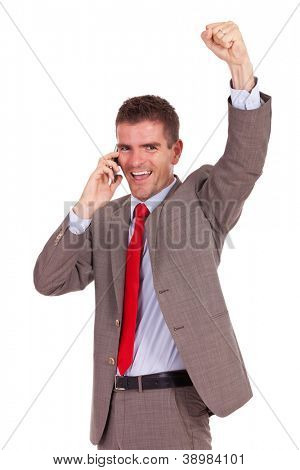 young business man speaking on the phone and cheering while looking at the camera
