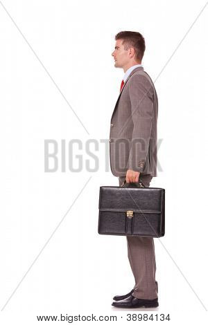 side view portrait of young business man holding briefcase in hand isolated on white