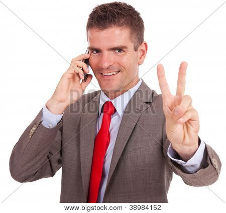 happy young business man speaking on the phone and showing victory sign to the camera