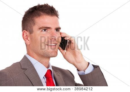 side view of a young business man talking on the mobile phone and looking away from the camera, isolated on white