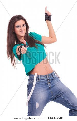 beautiful young woman dancer smiling at the camera, showing thumb up sign and pointing upwards. on white background