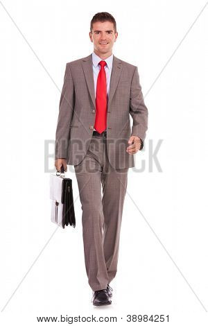 smiling young business man is walking with a briefcase against a white background