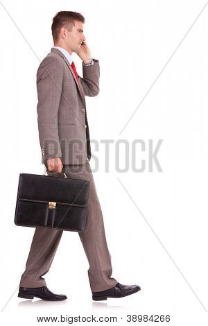 side view of a business man with his briefcase, talking on the mobile phone on white background