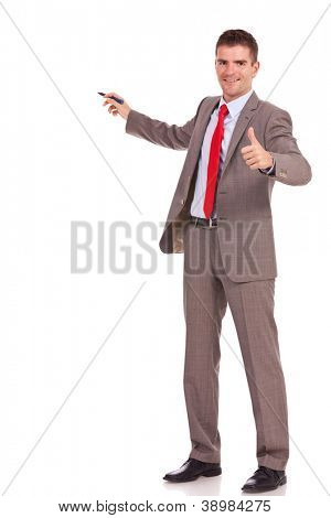 smiling young business man presenting something with marker pen and giving the thumbs up