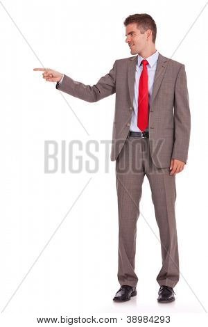 Side view, full length of a business man pointing at copyspace isolated over white background