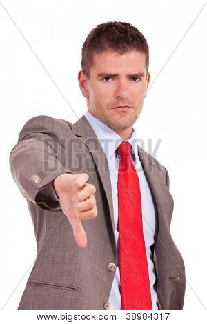 Young disappointed business man giving you the thumbs down sign, isolated over white background
