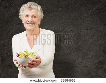 portrait of senior woman showing a fresh salad against a grunge wall
